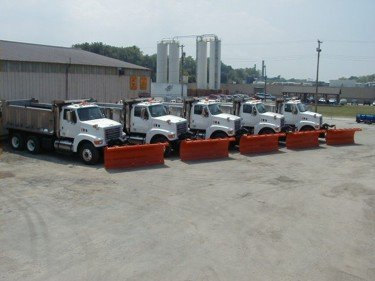 Multiple White One Ton Trucks With Red Plows