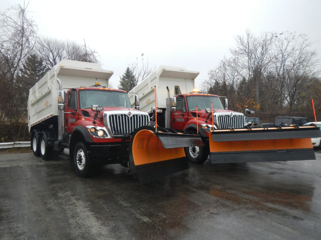 Two Red Concord Road Equipment With Orange Plows With White Dump Beds Raised