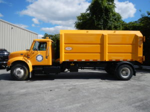 Concord Road Equipment Yellow Truck With Leaf Container Side